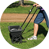 Woman fertilizing her backyard